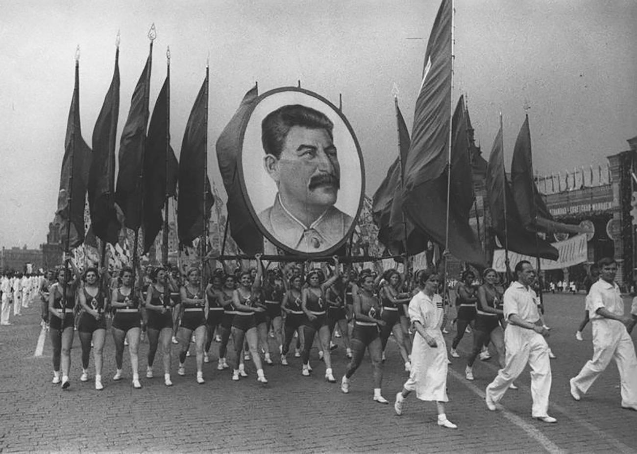 """La maggior parte della propaganda attuata durante le parate promuoveva anche l'immagine del leader, presente a ogni evento. Durante la Parata degli atleti del 1935 Stalin venne ribattezzato """"il miglior amico dei pionieri"""" e nel 1936 nacque un nuovo motto: """"Grazie, compagno Stalin, per la nostra infanzia felice"""""""