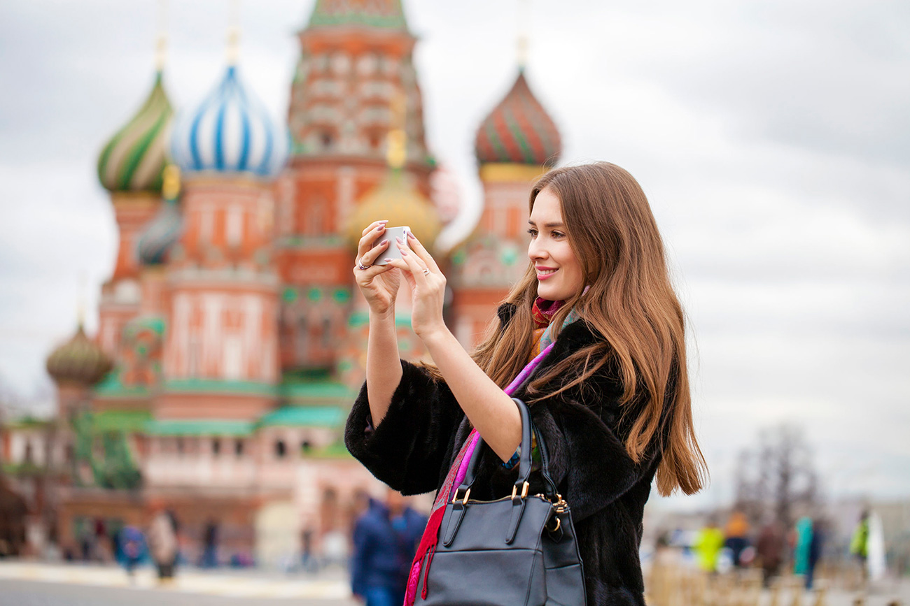 Young woman takes pictures on mobile phone on the background Red Square, Moscow Kremlin, Russia.