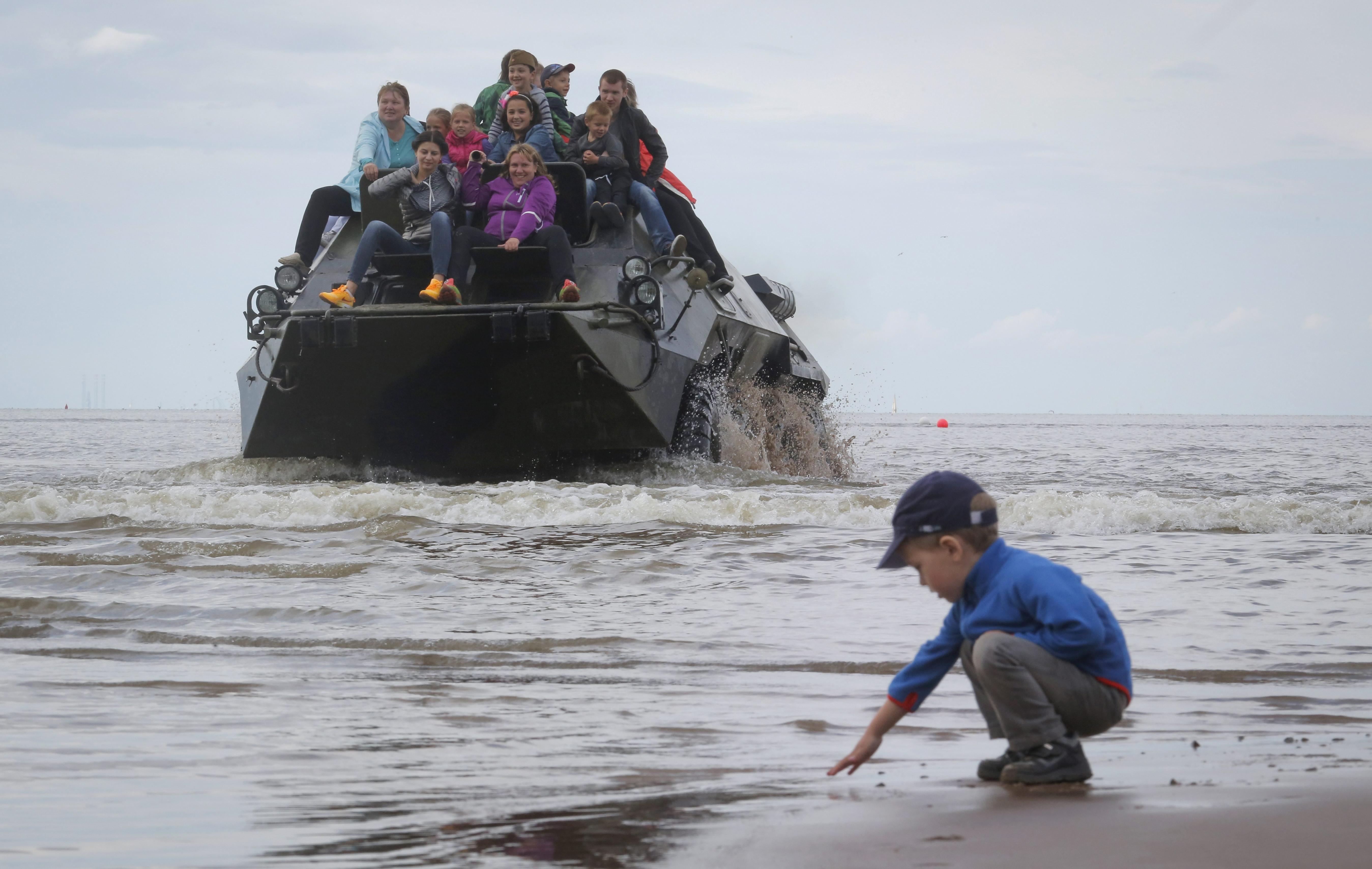 Хора се возят на бронетранспортьор по време на военно шоу във Финския залив.
