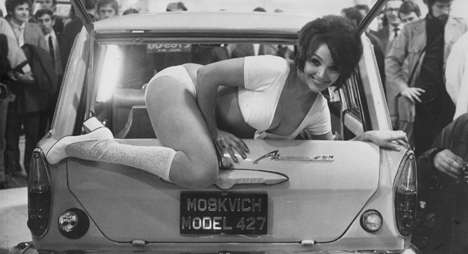 Model Julie Desmond climbs out of the back of a Moskvich 427 at a trade show, circa 1971