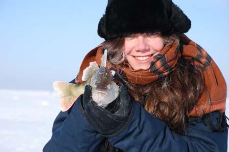 Marina segura um ômul, peixe encontrado apenas nas águas do lago Baikal Foto: arquivo pessoal
