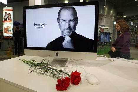 Flores diante de uma tela de computador com o retrato de Steve Jobs em loja da Apple em São Petersburgo Foto: Aleksandr Demianchuk/Reuters/Vostock-Photo