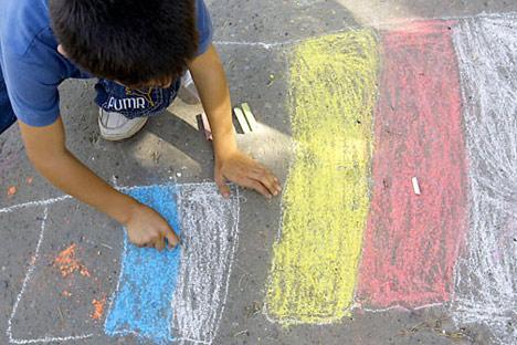 Un niño osetino dibujando las banderas de Rusia y Osetia del Sur. Foto de AP