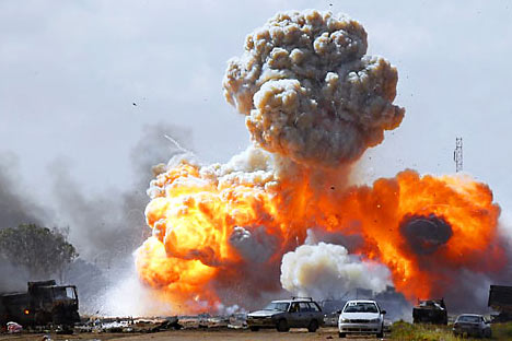 Vehicles belonging to forces loyal to Libyan leader Muammar Gaddafi explode after an air strike by coalition forces, along a road between Benghazi and Ajdabiyah. Source: Reuters / Vostock Photo