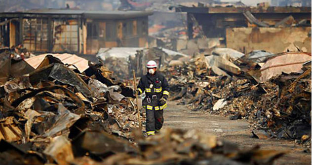 Rescue worker walks through a destroyed residential area of tsunami-hit Otsuchi March 14, 2011. In the town of Otsuchi in Iwate prefecture, 12,000 out of a population of 15,000 have disappeared following Friday's massive earthquake and tsunami.    So