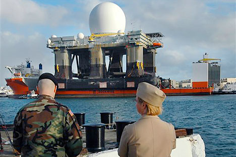 Military personel watch as the Sea-Based X-Band Radar sails into Pearl Harbor, Hawaii, aboard the MV Blue Marlin. The 280-foot tall Sea-Based X-band Radar is so powerful it can identify baseball-sized objects from thousands of miles away. US army was