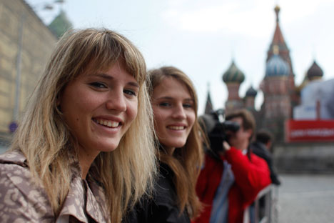 Twin sisters Jennifer, left, and Jessica, pose for a photo in front of St. Basil's Cathedral in the Red Square in Moscow. Photo: AP