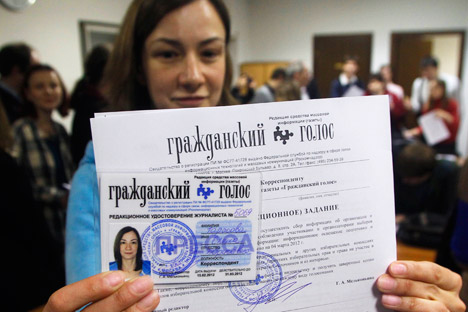 A volunteer observer, Yelena Tarasova, with her reporter's ID for Citizen's Voice, a newspaper issued by Golos. Source: AP