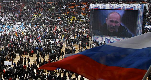 Russian Prime Minister Vladimir Putin is seen on a giant screen addressing a massive rally in his support at the Luzhniki stadium in Moscow, Russia, Thursday, Feb. 23, 2012. Tens of thousands of people marched along the Moscow River and then packed a