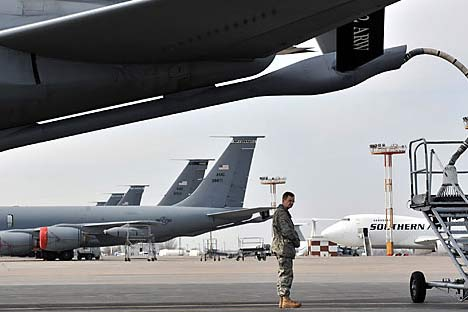 A US soldier stands near a plane bound for Afghanistan, as it fuels up at the Manas Transit Center some 30kms from Bishkek.   Source: AFP/East News