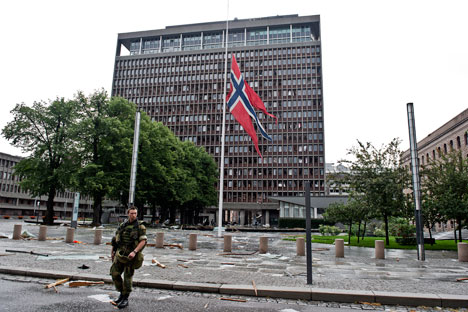 A soldiers passes by a Norwegian flag flying at half mast in front of the government headquarters building on July 23, 2011, a day after twin attacks here and on a youth camp, Norway's deadliest post-war tragedy. Source: AFP/East News