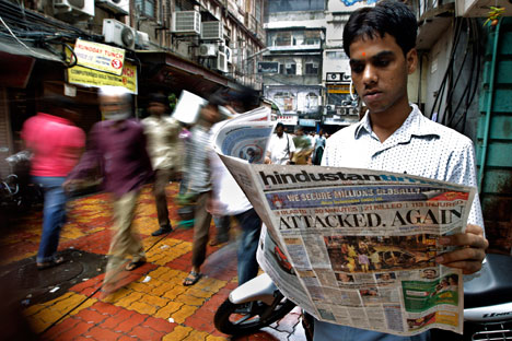 A man reads a newspaper with details of the bomb explosions at Zaveri bazaar area, near one of the bomb explosion sites, in Mumbai, India. Source: AP