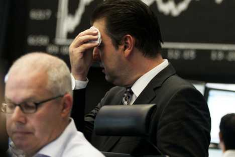 Market analyst wipes his face at the German stock exchange in Frankfurt, central Germany, Friday, Aug. 5, 2011. Europe's debt crisis and fears over the U.S economy battered markets once again Friday, challenging vacationing European leaders to find a