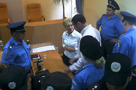 Ukrainian police officers surrounding Yulia Tymoshenko to detain her in the courtroom during a hearing Friday. Source: Alexander Prokopenko / Reuters