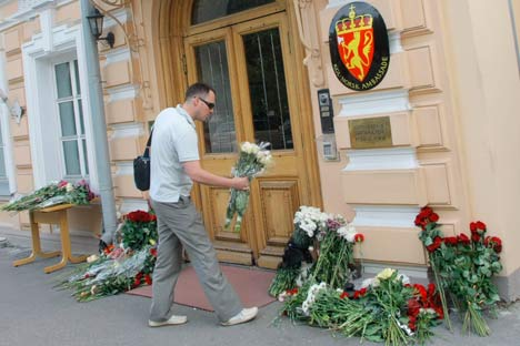 A man lay flowers in front of the Embassy of Norway in Moscow, in memory of the explosion and shooting victims. (AP Photo/Mikhail Metzel)