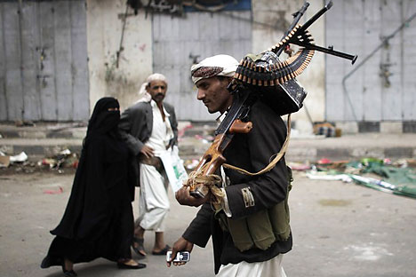 Passers-by look on as an armed tribesman loyal to tribal leader Sadiq al-Ahmar mans a checkpoint near al-Ahmar's house in Sanaa June 13, 2011. Source: Reuters/Vostock photo