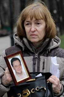 Natalia Magnítskaia sostiene el retrato de su hijo. Foto de AP