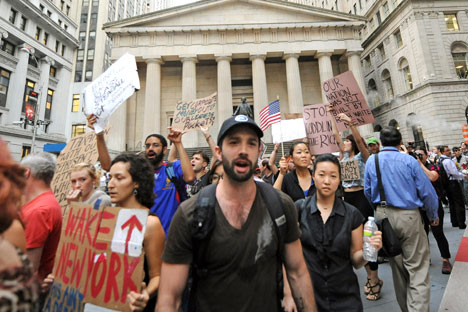 "Protestors march past Federal Hall on Wall Street, Monday, Sept. 26, 2011, in New York. The ""Occupy Wall Street"" protest is in its second week, as demonstrators speak out against corporate greed and social inequality. Source: AP"