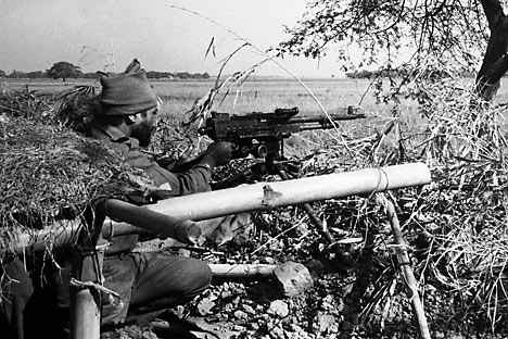 An Indian Army machine gunner fires at Pakistani positions in a village across an open field, 1,500 yards inside the East Pakistan border at Dongarpada on Dec. 7, 1971