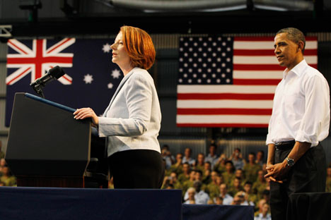 U.S. President Barack Obama looks at Australian Prime Minister Julia Gillard speak to Australian troops and U.S. Marines at Royal Australian Air Force Base in Darwin, Australia, Thursday, Nov. 17, 2011. Source: AP