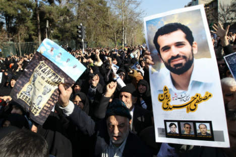 Iranians hold a portrait of assassinated nuclear scientist Mostafa Ahmadi-Roshan and a wanted poster with portraits of US President Barack Obama, German Chancellor Angela Merkel, French President Nicolas Sarkozy and British Prime Minister David Camer