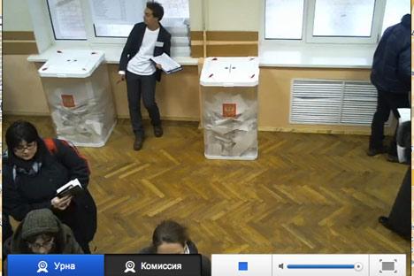 Ein Wahlbeobachter beaufsichtigt die Wahlurnen. Foto: Wahllokal-Webcam