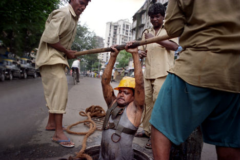 """A hundred oligarchs in India hold assets equivalent to 25 percent of the country's GDP, while 800 million of their compatriots survive on less than a dollar a day"". A sewage worker in Mumbai. Photo: Jacob Carlsen"