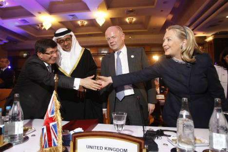 "U.S. Secretary of State Hillary Clinton (right) greets Turkish Foreign Minister Ahmet Davutoglu (left) during the ""Friends of Syria"" conference in Tunis on February 24. Source: Reuters"