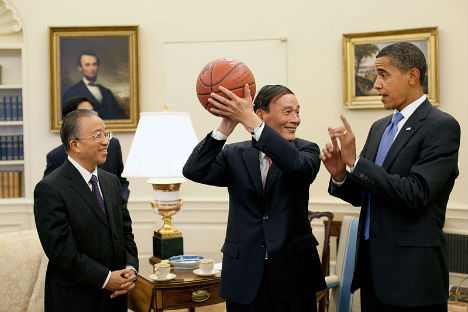 Chinese Vice Premier Wang Qishan, center, holds the autographed basketball given to him by President Barack Obama following their Oval Office meeting Tuesday, July 28, 2009, to discuss the outcomes of the first US–China Strategic and Economic Dialogu