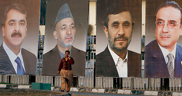 A man talks on his mobile phone as he walks past giant portraits of Afghanistan's President Karzai, Iran's President Ahmadinejad and Pakistan's President Zardari, along a road in Islamabad