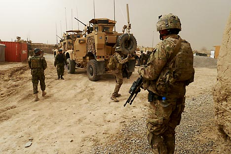 US soldiers keep watch at the entrance of a military base near Alkozai village following the shooting of Afghan civilians allegedly committed by a rogue US soldier in Panjwayi district, Kandahar province on March 11, 2012. Source: AFP/EastNews