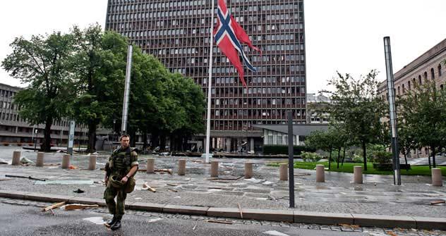 Soldado passa por bandeira norueguesa hasteada no que restou do mastro em frente à sede do governo um dia depois do duplo ataque extremista. Fonte: AFP/East News