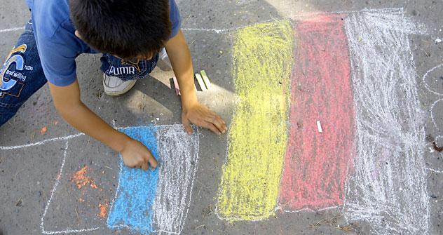 Un bambino disegna la bandiera della Russia e dell'Ossezia. Foto: AP