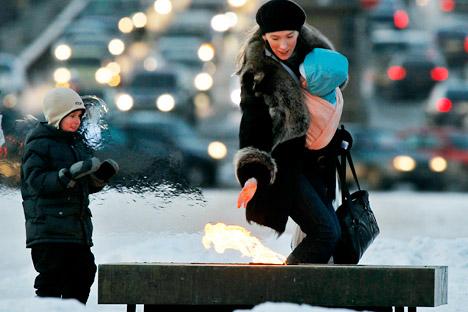 Una donna con i suoi due bambini si scalda le mani vicino alla Fiamma Eterna a San Pietroburgo (Foto: AP)