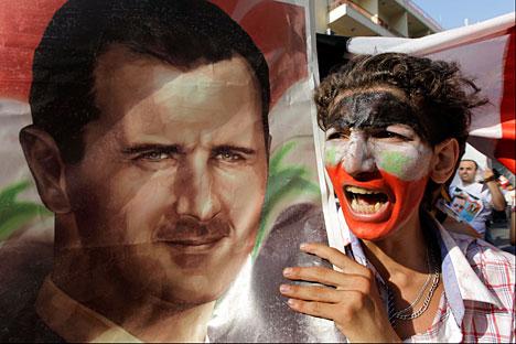 Un manifestante siriano grida slogan e mostra un'immagine del presidente siriano Bashar Assad, durante una manifestazione a favore di Assad di fronte l'Ambasciata di Siria a Beirut (Foto: AP/Bilal Hussein)