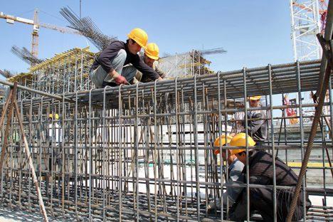 Alcuni operai stranieri al lavoro in un cantiere edile. Foto: Itar-Tass