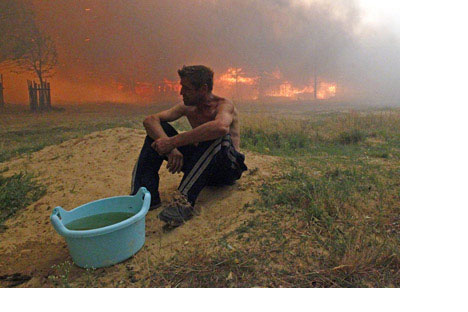 A man sits on the ground while a house burns due to severeheat outside the town of Vyksa, some 150 km south-west of theVolga city of Nizhny Novgorod, July 29, 2010.Source: Reuters/Vostock Photo