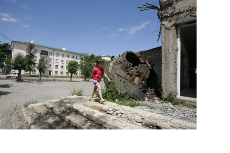 A girl walks past a tank turret, destroyedduring Georgia's war with Russia over SouthOssetia, in Tskhinvali, July 23, 2010  source Vostock photo