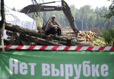 "A protester sits behind a barricade that reads ""No todeforestation"" at the site of Khimki highway constructionSource: ITAR-TASS"