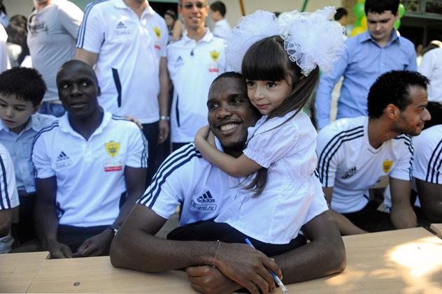 Samuel Eto'o, jogador do time russo FC Anji, abraça garota durante visita a uma escola em Makhachkalá, capital do Daguestão