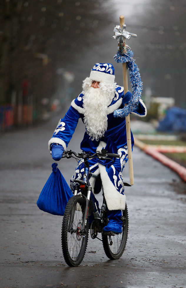 A man, dressed as Grandfather Frost, Russia's counterpart of Santa Claus, riding a bicycle at a city park in Stavropol in southern Russia on Dec. 29, 2011. Source: Reuters/Vostock-Photo