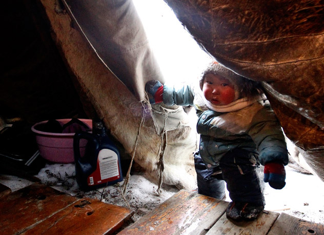 February 21, 2012 - A Nenet boy walks in a chum, the traditional Nenet tent, at a reindeer breeders' settlement in the Tundra region, 50 km (31 miles) from the town of Naryan-Mar, in the north of Russia. Source: Reuters/Vostock-Photo