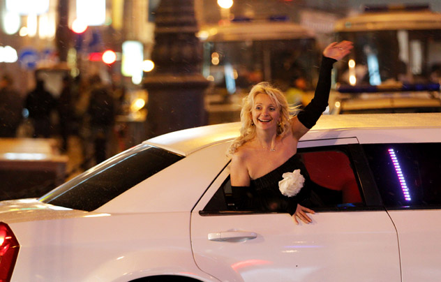 A Russian woman waves out of a car during celebrations for a wedding, while police officers in the background continue to bar the entrance to Pushkin Square after an opposition rally. The rally took place in Moscow on Monday 5 in response to Putin's victory in the presidential election. Riot police intervened during the protest and arrested dozens of participants, including prominent leaders of the opposition. Source: AP