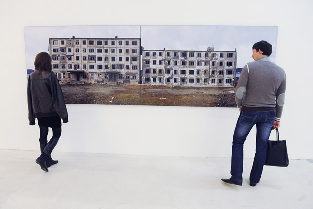 """Visitors admire Sergei Shestakov's work from his exhibition """"A Trip to the Future. Stop 2. Gudym"""" during the grand opening of the Photobiennale 2012, held at the Manezh Central Exhibition Hall. Source: RIA Novosti / Iliya Pitalev"""