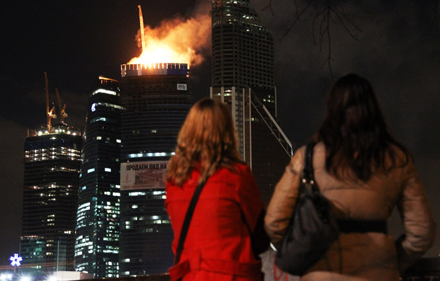 Two women look at the fire atop the under-construction eastern tower of the Federation Tower complex, planned to be Europe's tallest building, in Moscow, Russia,  on April 2, 2012. The flames were over 250 meter (880 feet) tall. The tower, when completed, is to be 360 meter (1150 feet) tall. Source: AP