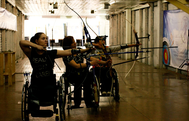 """Disabled wheelchair-bound Natalia Ryzhova (h), Svetlana Barantseva (c) and Margarita Sidorenko attend a training session of a local amateur archery club on the suburbs of Russia's Siberian city of Krasnoyarsk, May 3, 2012. Disabled people have the possibility of learning the sport of archery for free due to financial support from the newly created state regional centre of adaptive sport, according to club members. The banner reads """"Hello to participants of competitions"""".  Reuters/Vostock-Photo"""