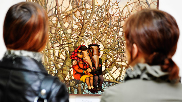 """Visitors admire the painting """"Fyeogyen and Golindukha"""" by Lidya Koz'mina, on display at the exhibition """"Russian national hallucinations"""" at the gallery """"PORTMAY"""" in Vladivostok, Russia. Source: ITAR-TASS"""
