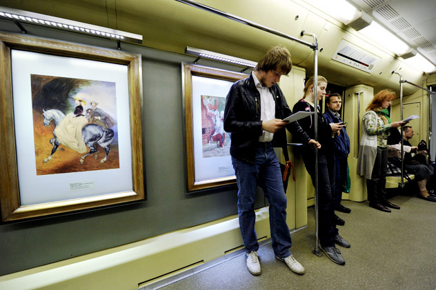 """Passengers on a carriage of the subway train """"Akvarel' (Water-Color),"""" which displays reproductions of some of the masterpieces from the Tretyakov Gallery. 35 paintings by Mikhail Vrubel, Karl Bryullov, Alexander Deineki and other 19th and 20th century artists were chosen as subjects of the train-exhibition. Source: RIA Novosti / Alexey Kudenko"""