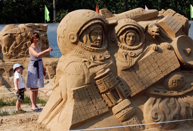 """A woman and a boy look at a creation, in reference to space exploration, at the """"Wheel of History"""" exhibition of sand sculptures in Russia's Siberian city of Krasnoyarsk, June 18, 2012. Sand sculptures, created by Siberian artists and depicting space exploration, the personality of Leonardo da Vinci, the Olympic Games, the Patriotic War of 1812 against the army of Napoleon Bonaparte and other topics, will be on exhibit all summer, according to organizers. Source: Reuters"""