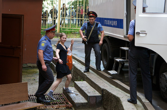 """Maria Alekhina, second left, a member of feminist punk group Pussy Riot is escorted form a court room in Moscow, Russia, Friday, July 20, 2012. The trial of feminist punk rockers who chanted a """"punk prayer"""" against President Vladimir Putin from a pulpit inside Russia's largest cathedral started in Moscow on Friday amid controversy over the prank that divided devout believers, Kremlin critics and ordinary Russians. AP Photo / Alexander Zemlianichenko"""
